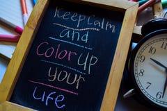 Halten Sie Ruhe und färben Sie herauf Ihr Leben auf buntem handgeschriebenem der Phrase auf Tafel, Wecker mit Motivation und Bild stockfoto