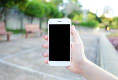 Halten von Smartphone mit schwarzem Schirm lizenzfreies stockbild