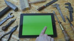 Halten von Tabletten-PC im Querformat mit Werkstatttabelle mit Zimmereiwerkzeugen im Hintergrund Mannhand unter Verwendung der Ta stock footage