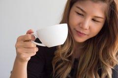 Haltene und aufpassende Kaffeetasse des asiatischen Mädchens der Nahaufnahme im Café lizenzfreies stockbild