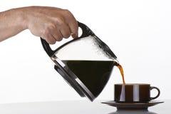 Haltener und auslaufender Kaffee des Mannes Hand Stockfoto