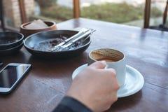 Haltener und trinkender Kaffee einer Frau stockfotos