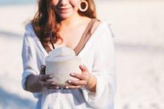 Haltener und trinkender Kokosnusssaft einer sch?nen asiatischen Frau auf dem Strand stockfotos