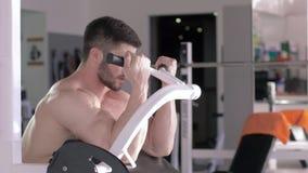 Halterofilismo, desportista muscular atrativo que faz exercícios do poder nos músculos das mãos no simulador durante a força vídeos de arquivo