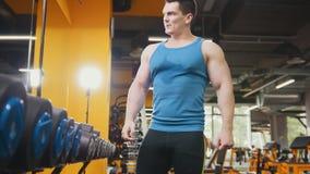 Halterofilismo no gym - o homem desportivo muscular novo tem o resto após a formação Imagens de Stock Royalty Free