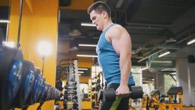 Halterofilismo no gym - o homem desportivo novo executa o treinamento para o braço Fotografia de Stock
