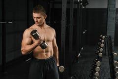 Halterofilista atlético do homem do poder considerável que faz exercícios com peso imagens de stock