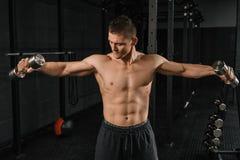 Halterofilista atlético do homem do poder considerável que faz exercícios com peso foto de stock royalty free