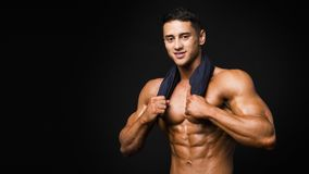 Halterofilista de sorriso forte atlético com a toalha sobre o fundo escuro fotografia de stock