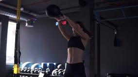 Halterofilista fêmea no sportswear que faz o crossfit para malhar com o sino da chaleira de 10 quilos Esporte, equipamento do gym filme