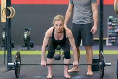 Halterofilista fêmea que levanta peso em um gym Imagens de Stock