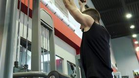 Halterofilista masculino considerável novo forte contratado com a máquina do exercício no gym vídeos de arquivo