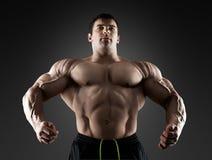 Halterofilista muscular considerável que levanta sobre o fundo preto Foto de Stock