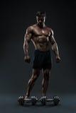 Halterofilista muscular impressionante que levanta sobre o fundo preto Foto de Stock Royalty Free