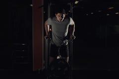 Halterofilista muscular que dá certo no gym que faz exercícios em barras paralelas fotos de stock