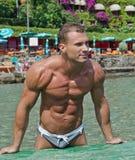 Halterofilista novo considerável na praia Imagem de Stock