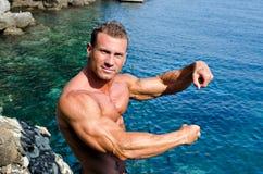 Halterofilista novo considerável pelo mar que mostra os braços Fotografia de Stock Royalty Free