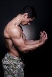 Halterofilista novo que dobra os músculos Fotos de Stock