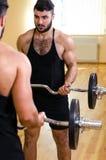 Halterofilista que dá certo o bíceps com o barbell na frente do espelho Imagens de Stock