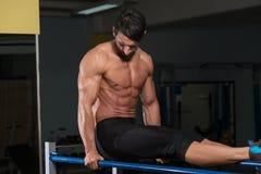 Halterofilista que exercita em barras paralelas Fotografia de Stock