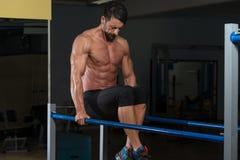 Halterofilista que exercita em barras paralelas Fotografia de Stock Royalty Free