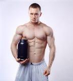 Halterofilista que guarda um frasco plástico preto com proteína do soro no fundo branco imagens de stock royalty free