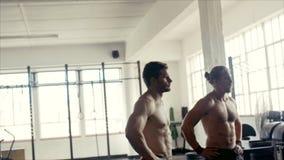 Halterofilistas que tomam uma ruptura após o exercício intenso no gym filme
