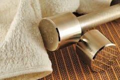 Haltères et serviette éponge sur le tapis en bambou Photo stock