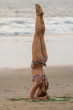 Haltung shirshasana Eine junge Frau in einem Bikini nimmt an Yoga auf dem Strand teil Lizenzfreie Stockbilder