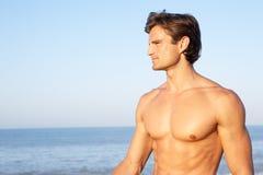 Haltungen des jungen Mannes auf Strand Lizenzfreies Stockbild