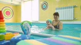 Halvåret behandla som ett barn flickan på hennes första simma kurs stock video