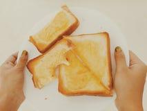 Halv äten ost på rostat bröd på en platta fotografering för bildbyråer