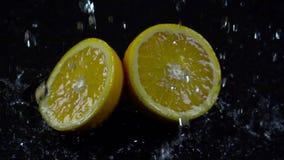 Halv apelsin med färgstänk av vatten på en svart bakgrund långsam rörelse stock video