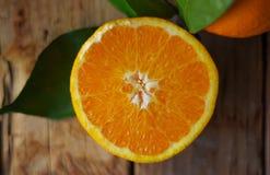 Halv apelsin med tjänstledigheter på tabellen Fotografering för Bildbyråer