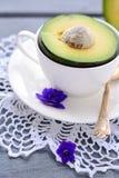 Halv avokado i en vit kopp Royaltyfria Bilder
