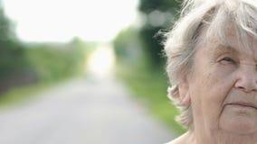 Halv framsida av den allvarliga äldre kvinnan utomhus stock video