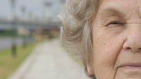 Halv framsida av den allvarliga mogna gamla kvinnan utomhus lager videofilmer