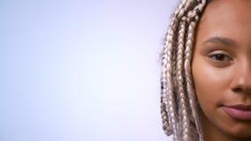 Halv framsida av den unga afrikanska flickan med dreadlocks som ler och ser kameran, vit bakgrund stock video