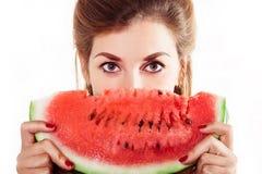 Halv framsida för härliga flickaräkningar en skiva av vattenmelon i studio Royaltyfri Bild