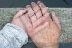 Halv-genomskinlig mans hand på en kvinnas hand som ett tecken av avskedet vid avskiljande eller död arkivbild