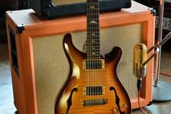 Halv Hollowbody för tappning elektrisk gitarr med fotoet för materiel för rörförstärkare- och för bandmikrofon studio royaltyfria bilder