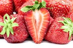 Halv jordgubbe bredvid hela bär Royaltyfria Bilder