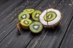 Halv kiwi och kokosnöt Arkivfoto