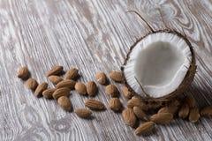 Halv kokosnöt och mandlar på en träställning royaltyfri bild