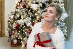 Halv längdstående av den härliga unga blonda flickan i den vita tröjan som poserar med gåvan nära julgranen royaltyfria foton