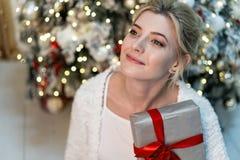 Halv längdstående av den härliga unga blonda flickan i den vita tröjan som poserar med gåvan nära julgranen arkivfoton