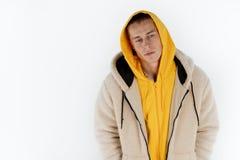 Halv l?ngdst?ende av den unga upprivna olyckliga mannen som b?r gult hoodieanseende mot vit bakgrund, copyspace f?r arkivfoto