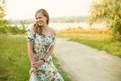 Halv längdstående av lyckligt le för charmig positiv iklädd lång vit sommarklänning för kvinna i solnedgångbakgrund Fotografering för Bildbyråer