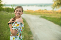Halv längdstående av lyckligt le för charmig positiv iklädd lång vit sommarklänning för kvinna i solnedgångbakgrund Arkivfoto