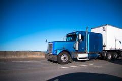 Halv lastbil för blå stor rigg med den halva släpet som flyttar sig framåt vid brett H Fotografering för Bildbyråer